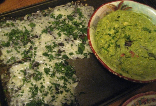 Cheesy nachos with chopped onion and cilantro and fresh guacamaole