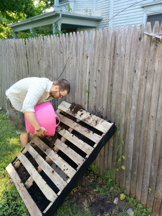 Dana filling the pallet garden with organic dirt, yum!